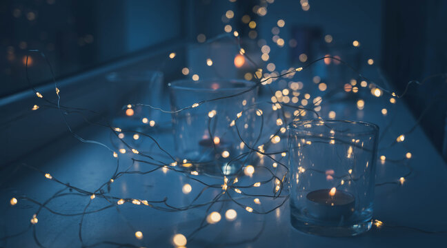 Close-up of burning tea candles in glasses on sill. Led lights garland. Hygge christmas decoration concept.