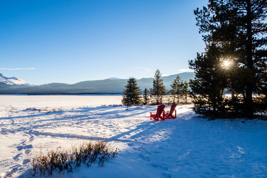 Winter view of two red Adirondack chairs at Maligne Lake in Jasper National Park, Canada