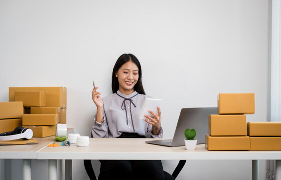 Young Asian woman business owner with many parcel boxes on the table happy online sales job, use your laptop, get an order from customers, take notes, and make arrangements for delivery by post