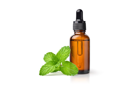 Peppermint essential oil in amber dropper bottle with fresh mint leaf isolated on white background.