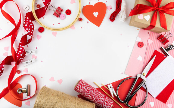 Valentine's Day background. Flat lei on a white background red ribbons, paper clips, hearts, gift, craft.