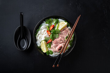 Pho Bo vietnamese soup with beef and rice noodles on a black background, top view