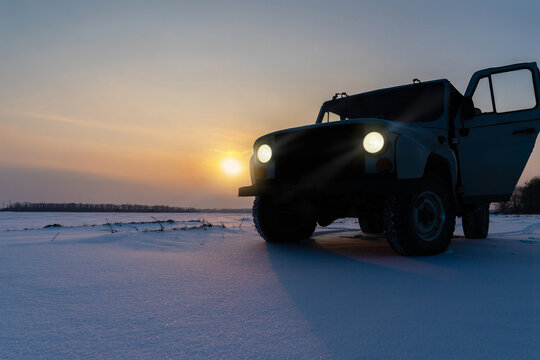 Truck in the snow. Sunset in a field covered with snow. The road is covered with snow.