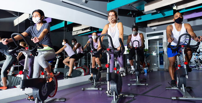 Men and women wearing protective masks ride stationary bike in a fitness club