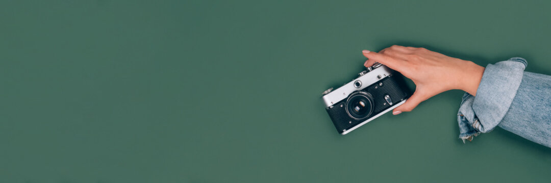 Banner with female hand holding vintage retro photo camera on green background with copy space for text. Trendy vintage photography, Online photography school concept. Selective focus