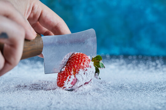 Woman cutting fresh strawberry on blue background with knife
