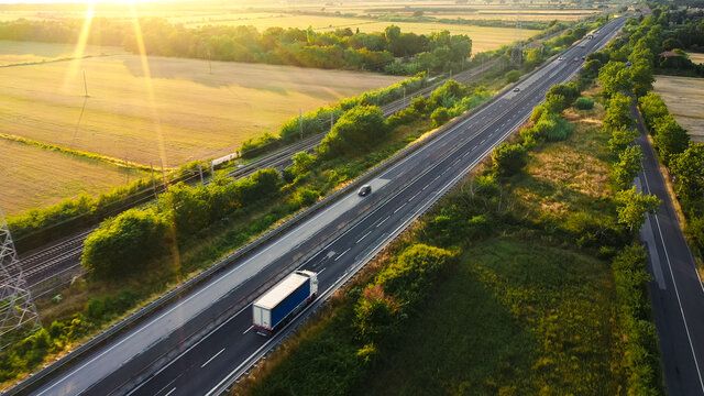 Aerial Drone Shot: Long Haul Semi Trucks Driving on the Busy Highway in the Rural Region of Italy. Agricultural Crop Fields and Hills in the Background