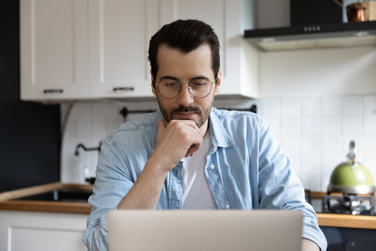 Consider a problem. Contemplative millennial man working from home ponder on data on pc screen. Doubtful male programmer choose effective way to get result think about possible error in code project