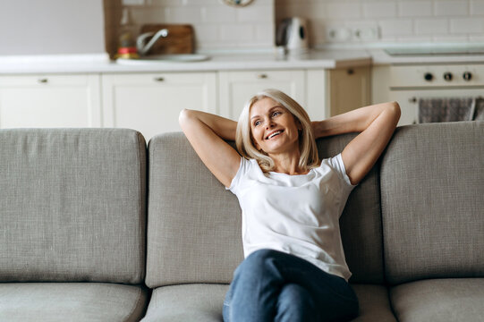 Happy mature caucasian woman is relaxing on the couch in living room at home. Middle aged woman enjoying weekend or leisure from homework sitting on sofa, looks away and smiling