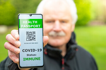 Senior man showing a health passport on a mobile phone, which indicates a vaccination against...