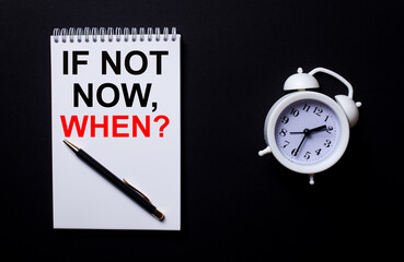 Question IF NOT NOW, WHEN is written in a white notepad near a white alarm clock on a black background.