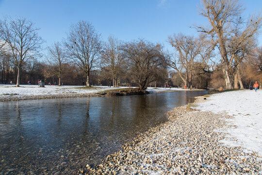 Winter Idylle im Englischen Garten, München: Der renaturierte Schwabinger Bach umgeben von alten Bäumen und Kies