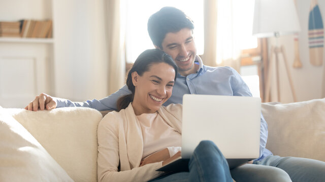 Close up overjoyed couple looking at laptop screen, sitting on cozy couch at home, smiling woman and man hugging, using computer, booking or shopping online, enjoying leisure time with device