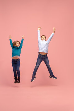 Freedom, style. Happy children isolated on coral pink studio background. Look happy, cheerful. Copyspace for ad. Childhood, education, emotions, facial expression concept. Jumping high, flying.