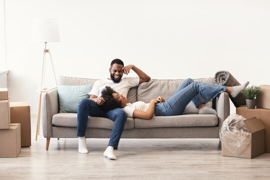 African American Couple Relaxing Among Moving Boxes In New Home