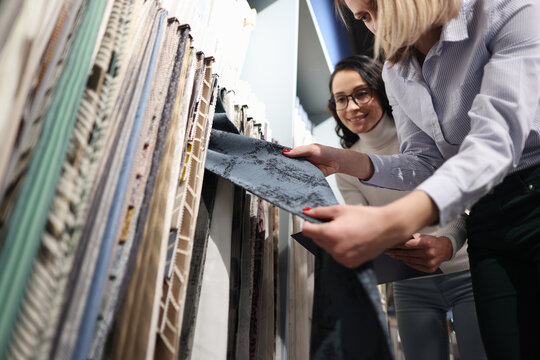 Seller demonstrates fabric samples to client closeup
