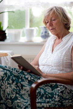 Seniorin lesend im Sessel