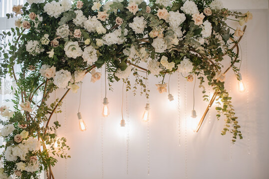 Beautiful decoration with flowers and lamps in wedding arch