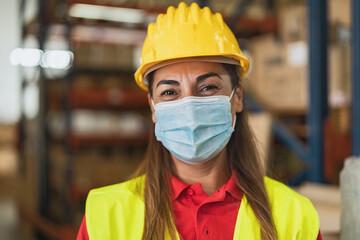 Happy Latin woman working in warehouse while wearing face mask during corona virus pandemic -...