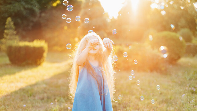 Child whirling, dancing plays on the meadow. Girl having fun with bubbles. Cute little longhair blonde girl dancing with soap bubbles at sunset park