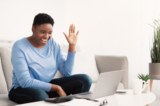 Black woman having videocall using laptop waving hand