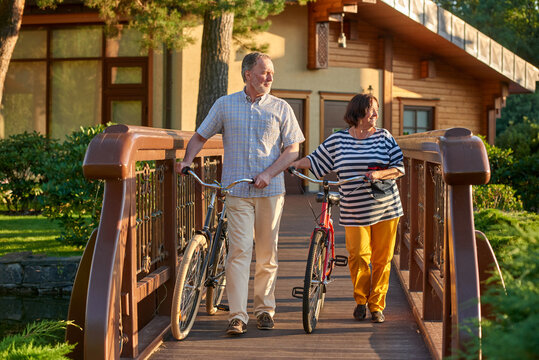 Retired man and his wife walk with bikes. Portrait of mature couple on the bridge.