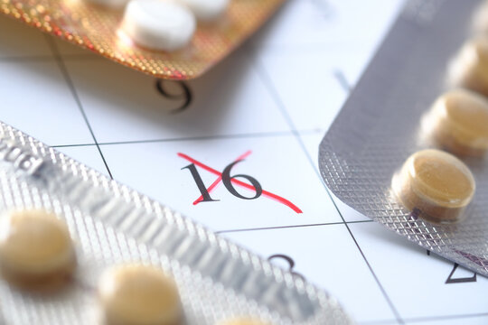 birth control pills and calendar with red mark on table