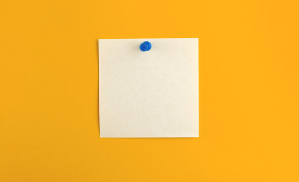 Pinned notepad sheet of square paper on isolated yellow background, for message and work letters