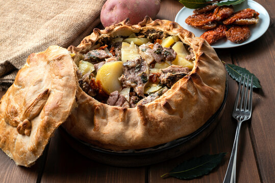 Panada Sarda, pietanza tipica della Sardegna a base di pasta cotta al forno e ripiena di agnello, patate e pomodori secchi, Cucina Italiana