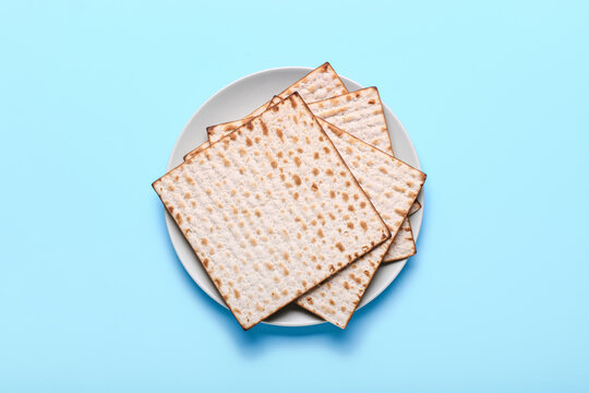 Plate with Jewish flatbread matza for Passover on color background
