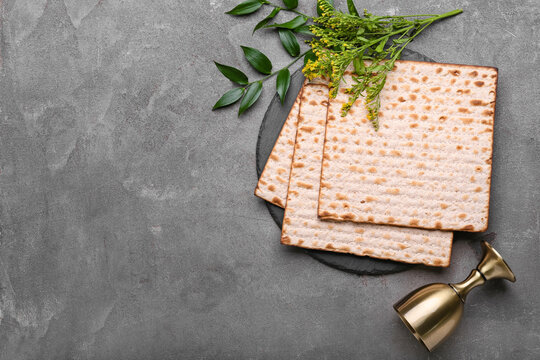Jewish flatbread matza for Passover and cup on grey background