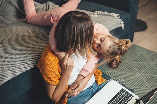 Caucasian mother is working on the floor using a laptop while her daughter is embracing her