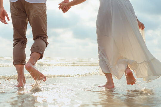 Love young couple barefoot running on the beach. Holiday and vocation concept.