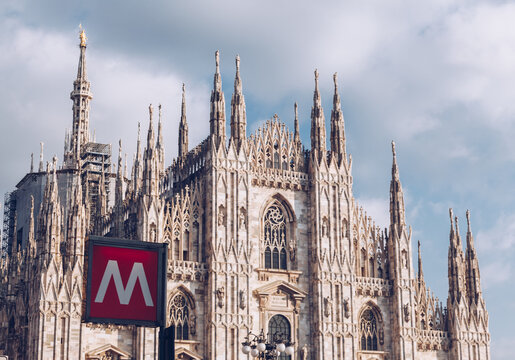 sign metro station with blurred Milan Cathedral church on the background - italy lombardy.