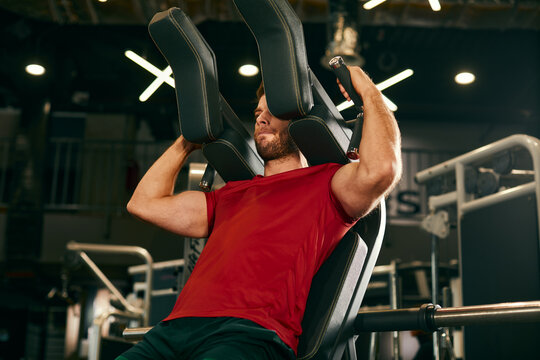 Athletic man doing legs exercise on squat machine at the gym  focus on the upper body