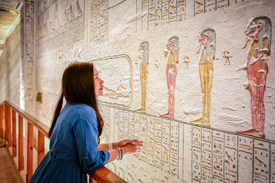 Luxor, Egypt - 02 11 2020: Asian women stand to admire the beauty of the ancient and mysterious Egyptian wall carving inside the cemetery in The Valley of the Kings.