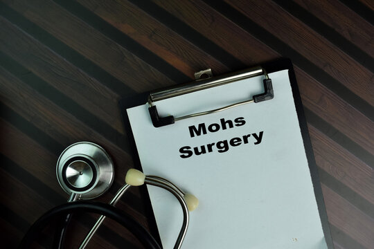 Mohs Surgery write on a paperwork isolated on Wooden Table.