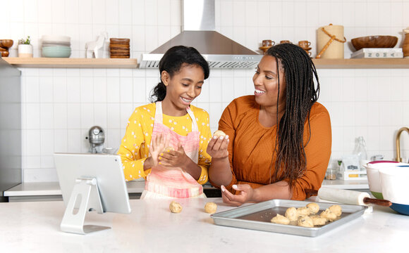 African American mother and daughter baking cookies in the kitchen