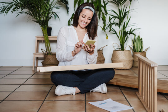 young woman assembling furniture at home reading instructions on mobile phone. DIY concept