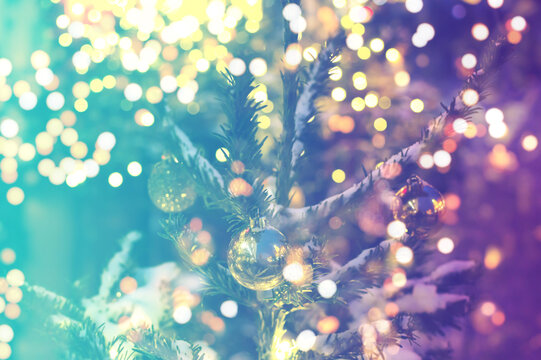 Christmas tree branches with balls and blurry lights background. Design for your ad, poster, banner