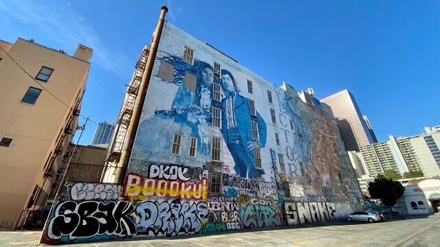 LOS ANGELES, CA, NOV 2020: looking up at artistic mural partially covered in graffiti tags on a building wall next to a parking lot in Downtown