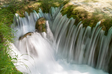 Wall Mural - a stream of water flowing down from the rocks