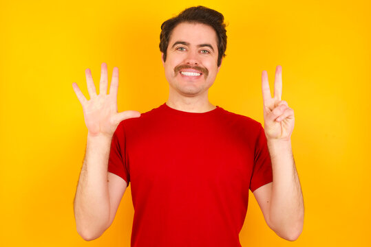 Young Caucasian man wearing red t-shirt standing against yellow wall showing and pointing up with fingers number seven while smiling confident and happy.