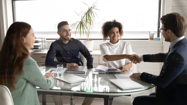 Happy diverse business partners shaking hands at meeting in modern boardroom, group negotiations, African American businesswoman and businessman making agreement, great deal, signing contract