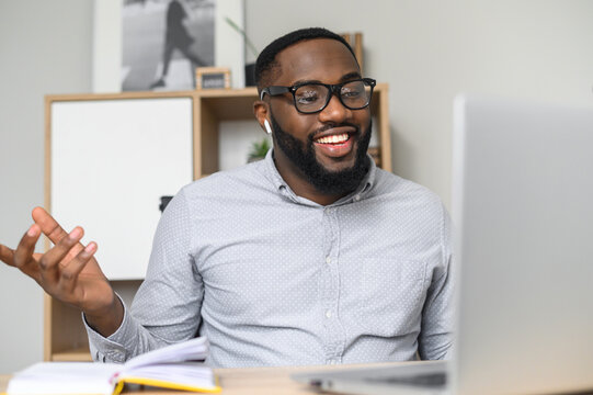 Handsome young African-American accountant in glasses discussing the business strategy with the teammates online, using the laptop for webinar, making a voice call, drawing on the white board