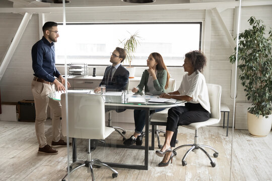Arabian executive leading corporate briefing with diverse employees in boardroom behind glass wall view, training staff, office workers listening to mentor coach, business partners group negotiation