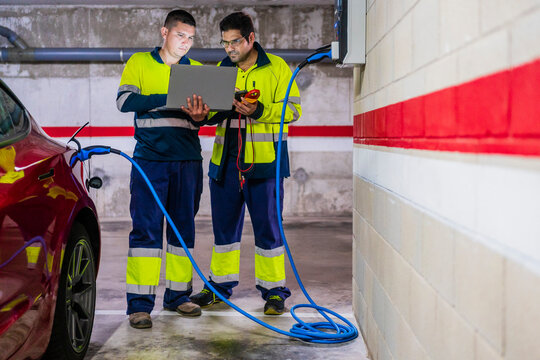 Male technicians using laptop while charging electric vehicle in auto repair shop