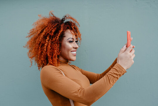 Smiling woman taking selfie while standing by gray wall