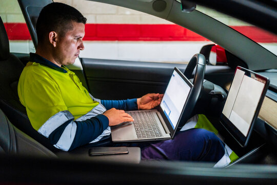 Male technician working on laptop for programming in electric car