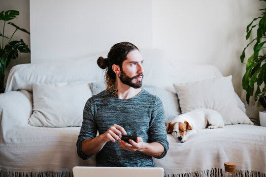 Man with laptop and mobile phone looking away while sitting by dog sleeping on sofa at home